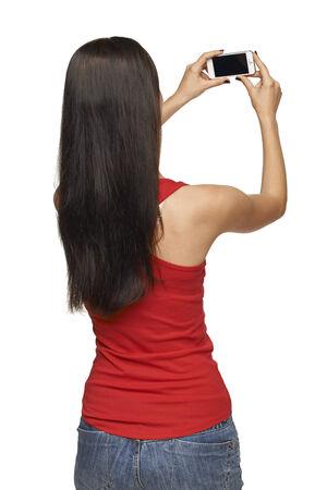 Terug oog van de jonge vrouw het nemen van foto's via mobiele telefoon, op witte achtergrond