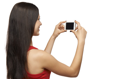 Happy young girl taking pictures of herself through cell phone, over white background