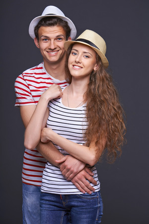 Beautiful young couple in summer hats hugging over gray background photo
