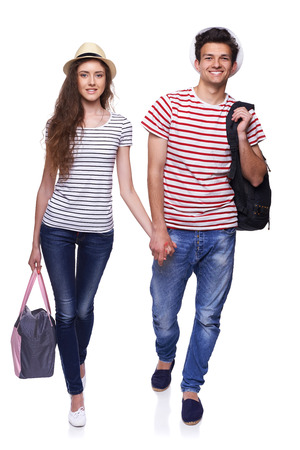 25 30 years old: Full length of young happy couple walking with travel bags with joined hands, isolated on white background Stock Photo