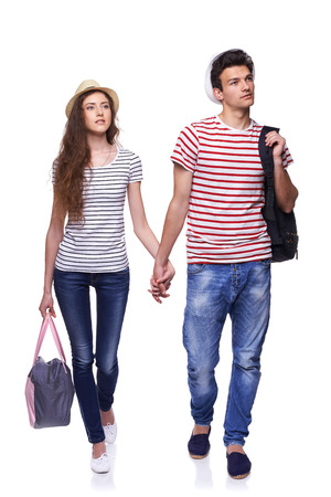 Full length of young couple walking with travel bags with joined hands looking way at copy space, isolated on white background