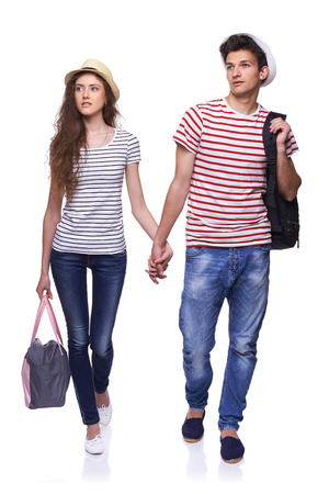 25 30 years old: Full length of young couple walking with travel bags with joined hands looking way at copy space, isolated on white background
