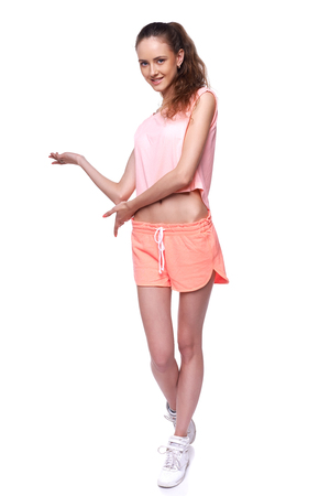 commercial activity: Pretty young sport woman standing in full length and showing blank copy space, on white background