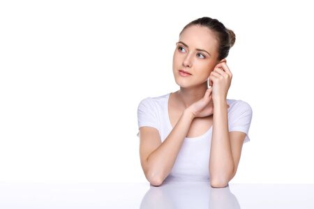 leaning on elbows: Young natural woman with clean face sitting at white table leaning on her elbows, over white background