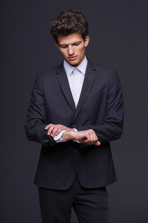 retardation: Confused business man looking on his wrist with no watch against dark background  Stock Photo