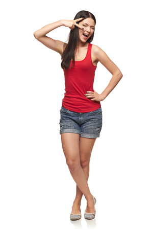 winking: Happy expressive young woman posing in full length, over white background Stock Photo