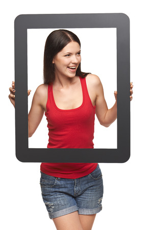 Bright young woman looking to side through frame, over white background photo