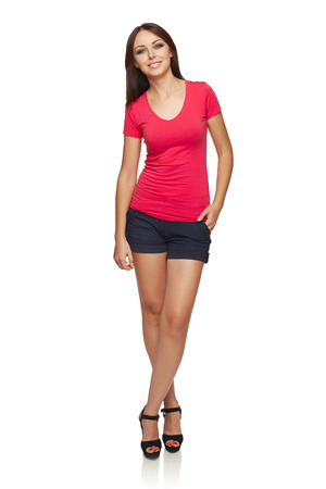 cuerpo entero: Todo el cuerpo de mujer joven en la parte superior de color rojo brillante y pantalones cortos de pie relajado con la mano en el bolsillo, sobre fondo blanco de estudio Foto de archivo