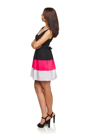 profile views: Side view of young female in dress standing full length looking away at blank copy space, looking away at blank space, isolated on white