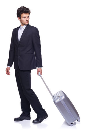 Full length of a businessman walking with a luggage, over white background photo