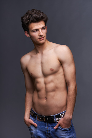 Male fashion model with modern haircut posing shirtless over dark