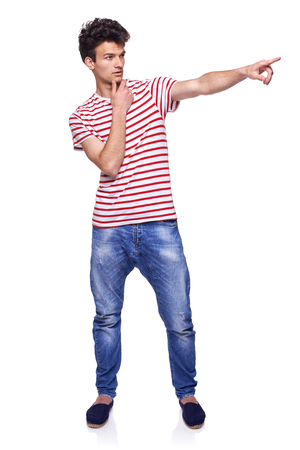 sideways: Full length of young trendy casual man pointing to the side on blank copy space, over white