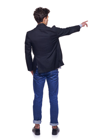 Full length back view of young trendy man pointing to the side on blank copy space, over white