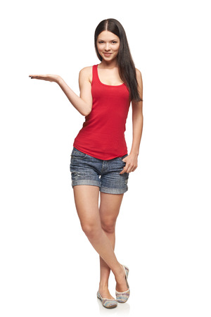 welcoming: Full length of beautiful woman showing holding on the palm blank copy space over white background