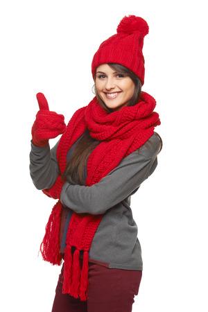 Zima, vánoční, koncepce svátků. Šťastný úsměv krásná žena v červeném klobouku, šátek a palčáky ukazující palec nahoru na bílém pozadí
