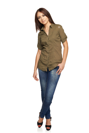 envisage: Young thinking woman in jeans and green shirt looking down, standing relaxed in full length, over white studio background