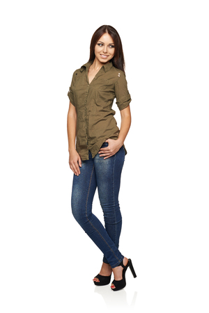 poised: Young smiling woman in jeans and green shirt standing relaxed in full length looking to the side, over white studio background