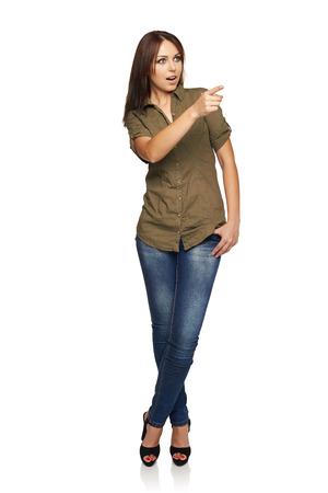 blusa: Mujer joven sorprendida con la boca abierta que apunta hacia el lado en el espacio de la copia en blanco, de pie en toda su longitud, sobre fondo blanco