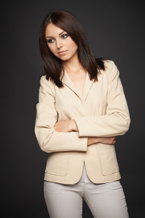 Pensive business woman in beige suit standing with folded hands looking down