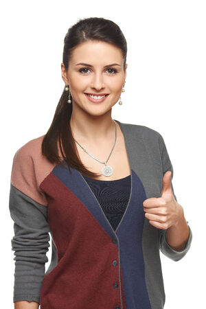 Smiling young woman in cardigan gesturing thumb up, looking at camera, over white background