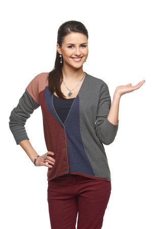 Smiling woman in autumn cardigan showing open hand palm with copy space for product or text Banque d'images