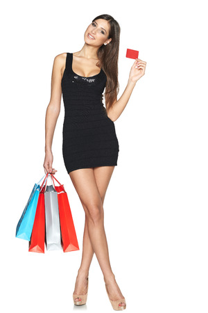 Lovely woman with shopping bags showing empty paper card, in full length over white background photo