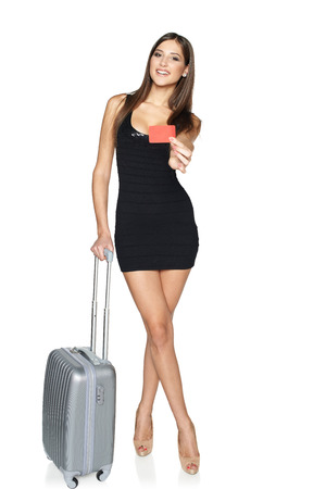 Woman tourist. Full length sexy young woman in black mini dress standing with suitcase and showing blank credit card, isolated on white background Stock Photo