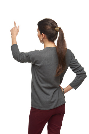 point: Back view of young woman in cardigan pointing at copy space, isolated on white