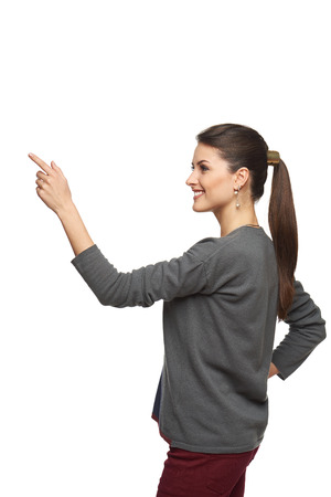 Side view of young woman in cardigan pointing at copy space, isolated on white photo