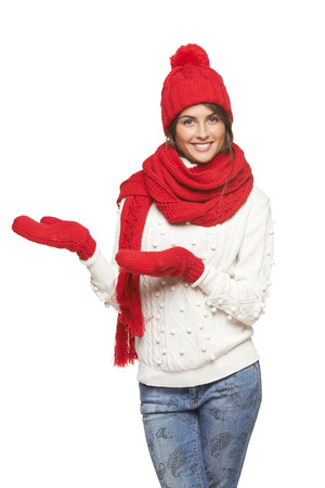 Winter, christmas, holidays concept. Smiling beautiful woman in red hat, scarf and mittens showing open hand palm with copy space for product or text, over gray background