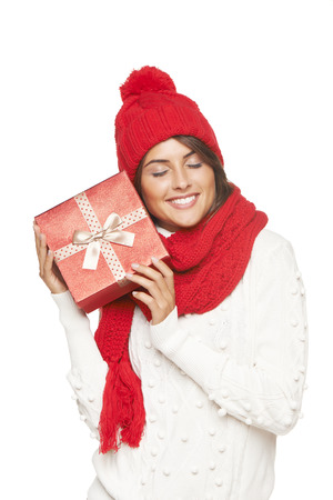 envisioning: Christmas gift. Smiling beautiful woman in winter red hat and scarf envisioning with closed eyes what is in the gift box, over white background