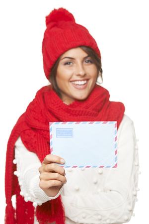 Christmas, winter mail concept. Happy laughing beautiful woman in winter red hat and scarf giving you mail envelope, over white background. Focus on envelope photo