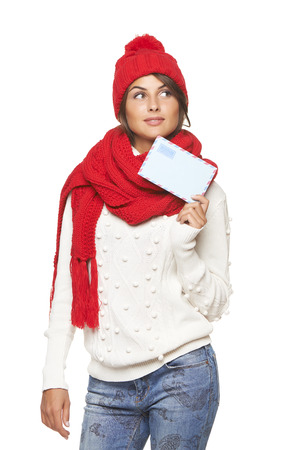 envisioning: Christmas, winter mail concept. Thinking woman in winter red hat and scarf holding mail envelope and looking up at blank copy space, over white background