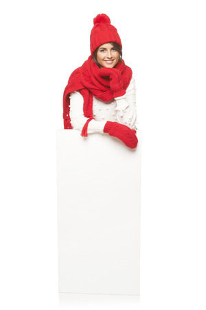 outerwear: Happy woman in winter outerwear standing in full length leaning on white banner at studio over white background