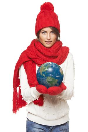 continente americano: Mujer hermosa de invierno en el sombrero rojo caliente, bufanda y guantes de la celebraci�n globo de tierra en sus manos, continente americano en el frente, sobre fondo blanco Sonriente