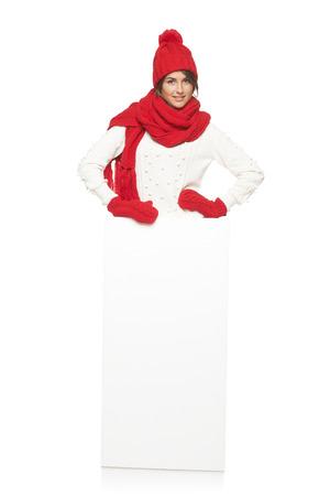 outerwear: Donna felice in tuta sportiva di inverno in piedi in piena lunghezza appoggiata sul banner bianco in studio su sfondo bianco