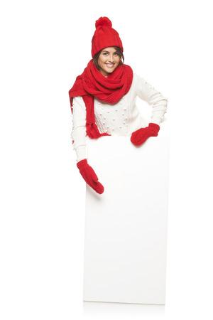 outerwear: Donna felice in tuta sportiva di inverno in piedi in piena lunghezza con la bandiera bianca e rivolte, in studio su sfondo bianco Archivio Fotografico