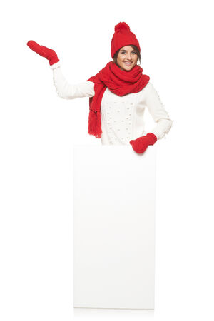 outerwear: Happy woman in winter outerwear standing in full length with white banner and pointing at blank copy space, at studio over white background