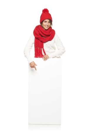 outerwear: Happy woman in winter outerwear standing in full length with white banner and pointing at it, at studio over white background