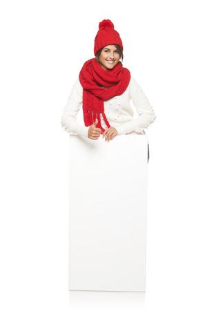 outerwear: Donna felice in tuta sportiva di inverno in piedi in piena lunghezza appoggiata sul banner bianco e gesticolano pollice in su segno, in studio su sfondo bianco