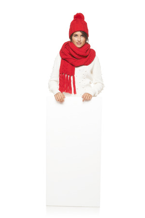 outerwear: Woman in winter outerwear looking skeptically standing in full length leaning on white banner at studio over white background