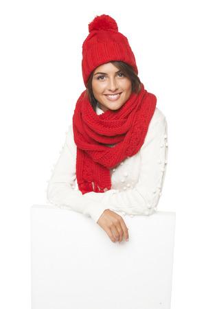 outerwear: Donna felice in tuta sportiva di inverno in piedi dietro e si appoggia sul banner bianco in studio su sfondo bianco Archivio Fotografico