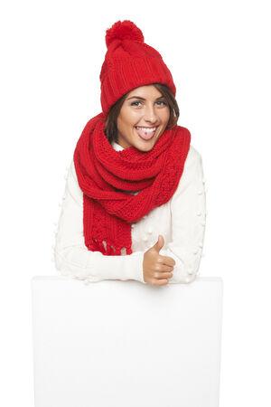 outerwear: Donna divertente in tuta sportiva di inverno in piedi appoggiata sul banner bianco e tirando il viso, gesticolano pollice in su, su in studio su sfondo bianco