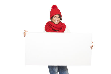Happy woman in winter outerwear holding white banner at studio over white background photo
