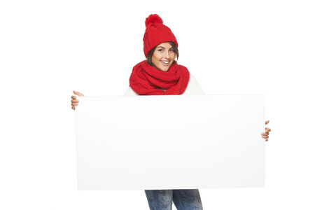 outerwear: Happy woman in winter outerwear holding white banner at studio over white background Stock Photo
