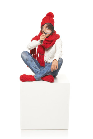 Winter seasonal search. Surprised woman wearing knitted warm red scarf, hat and socks sitting on blank billboard placard sign, looking through magnifying glass photo