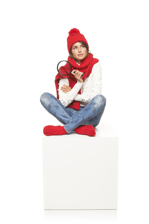 Winter seasonal search. Thinking woman wearing knitted warm red scarf, hat and socks sitting on blank billboard placard sign, holding magnifying glass and looking up at blank copy space photo