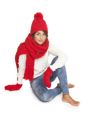 Winter, christmas, holidays concept. Smiling beautiful woman in red hat, scarf and mittens sitting in floor, over white background