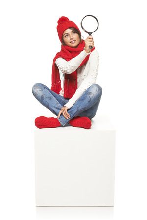woman wearing knitted warm red scarf, hat and socks sitting on blank billboard placard sign, looking through magnifying glass photo