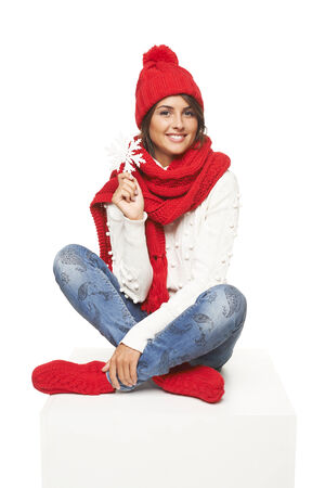 red snowflake background: woman wearing knitted warm red scarf, hat and socks sitting on blank billboard placard sign and showing snowflake, against white studio background Stock Photo